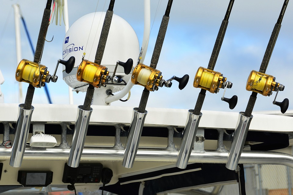 Heavy baitcasting rods sitting in rod holders on a boat.