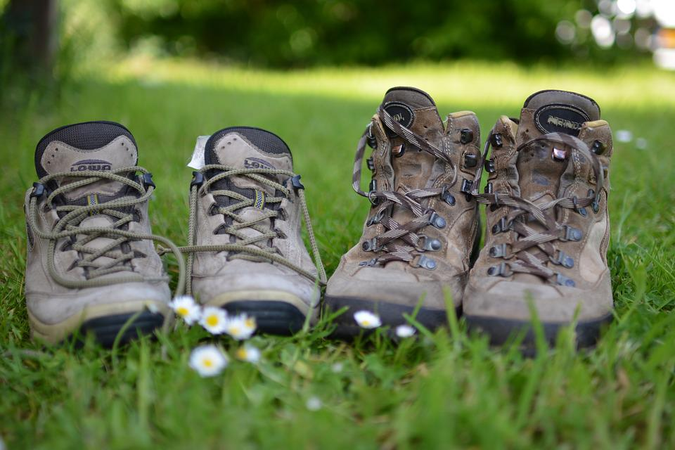 two pairs of hiking boots sitting untied in green grass