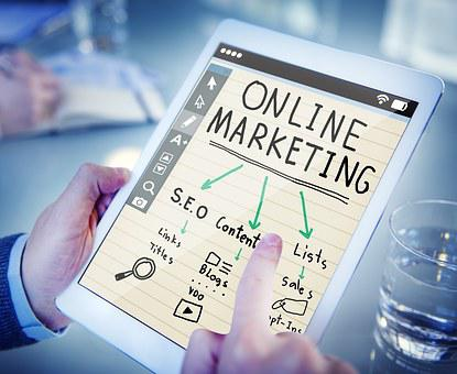 A hand holding a board with the inscription ONLINE MARKETING with grren arrows pointing towards SEO, Content, hits, etc.