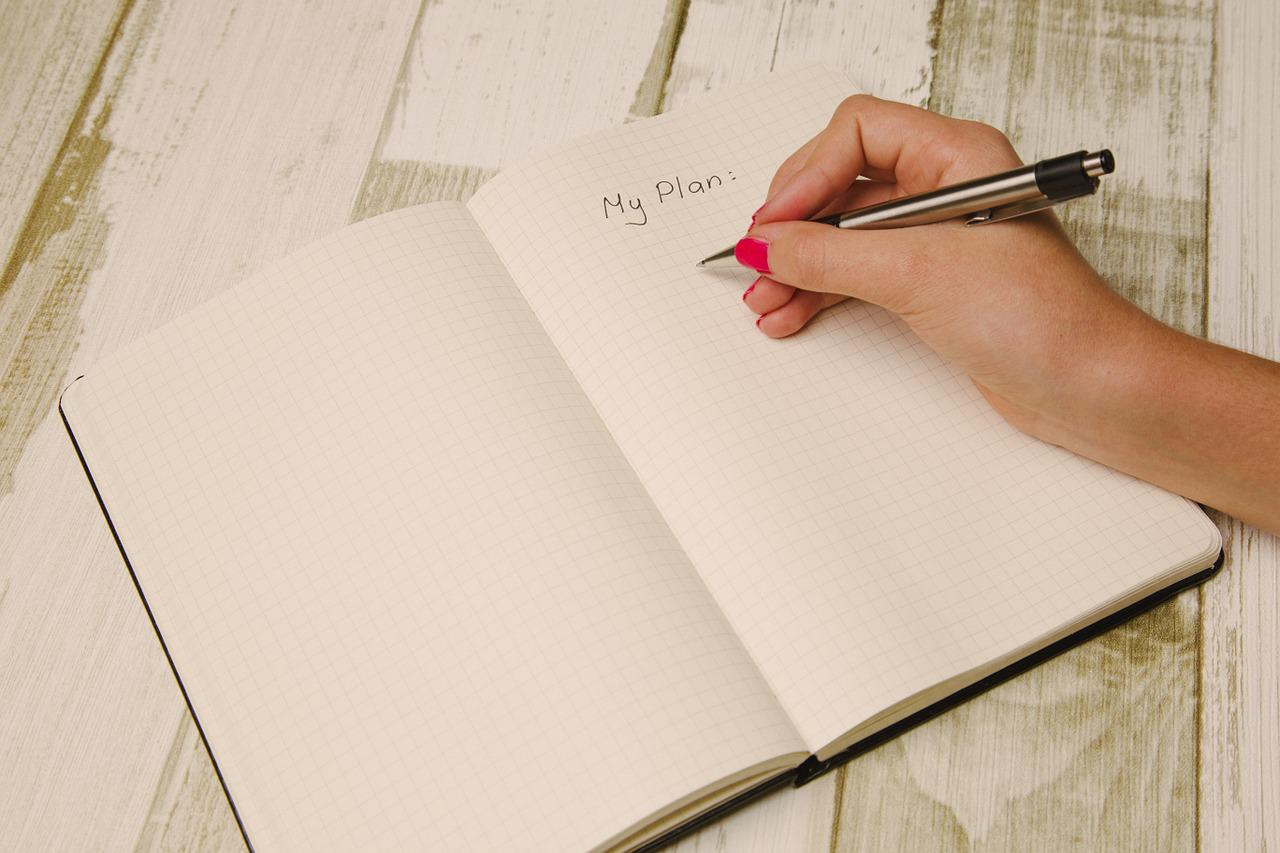woman writing plans on a notebook