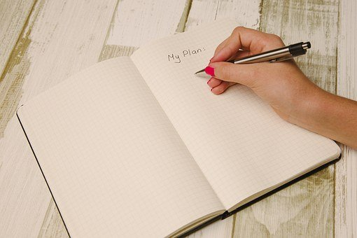 A woman's hand writing on a planner