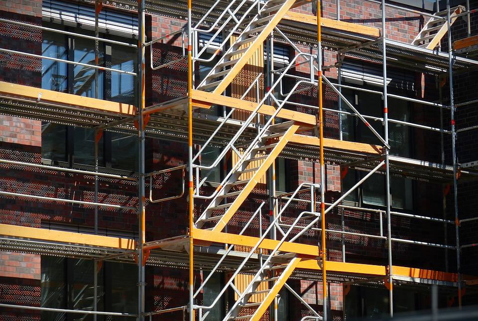 Metal scaffolding alongside a brick building.