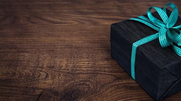 A black box wrapped with a blue ribon and laid on a brown desk to signfiy my gift for signing up