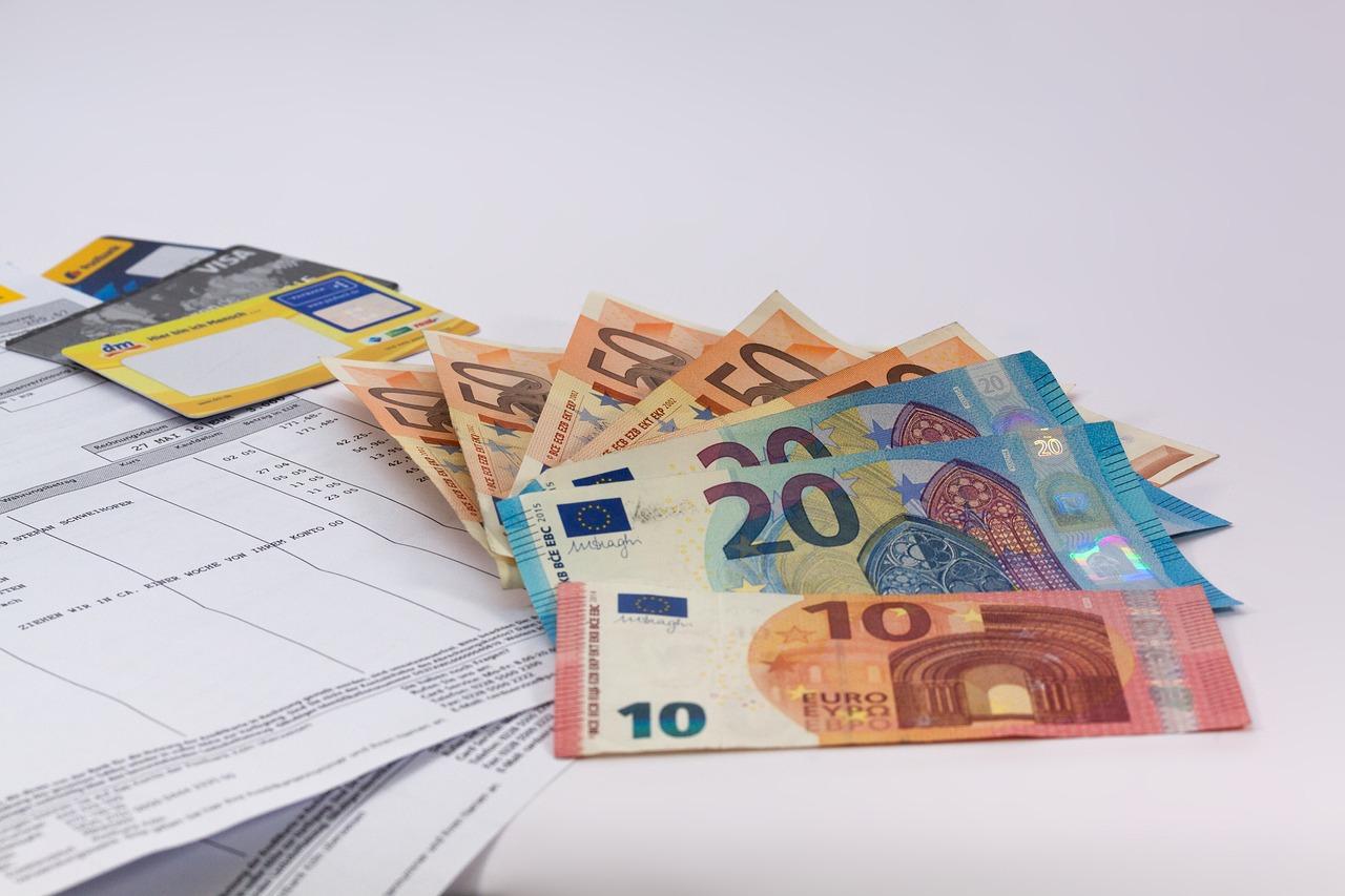 Geldscheine und Kreditkarten neben einer Rechnung