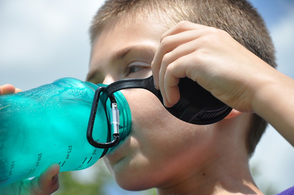 kid drinking from a water bottle with ice in it