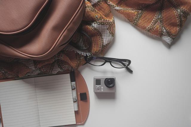 occhiali, borsa e taccuino