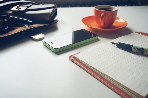Purse and other items on a freelancer's table signifying How to Make a Living From Home: 6 (Legit) Online Job Ideas