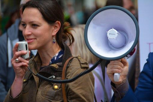 A smiling woman talking into the microphone of a megaphone held by a man