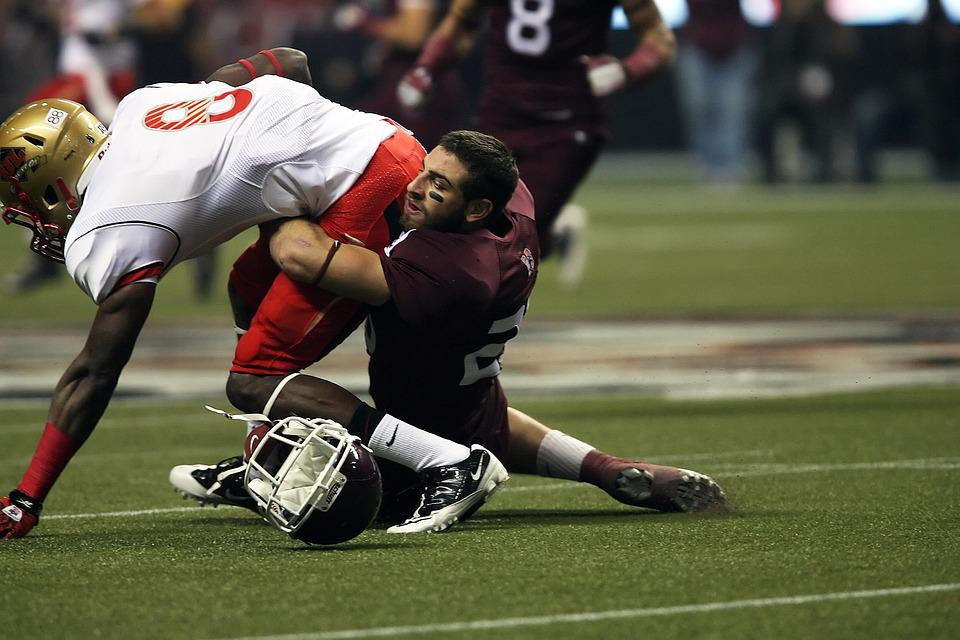 Canadian football player being tackled by another football player, and a helmet has come loose