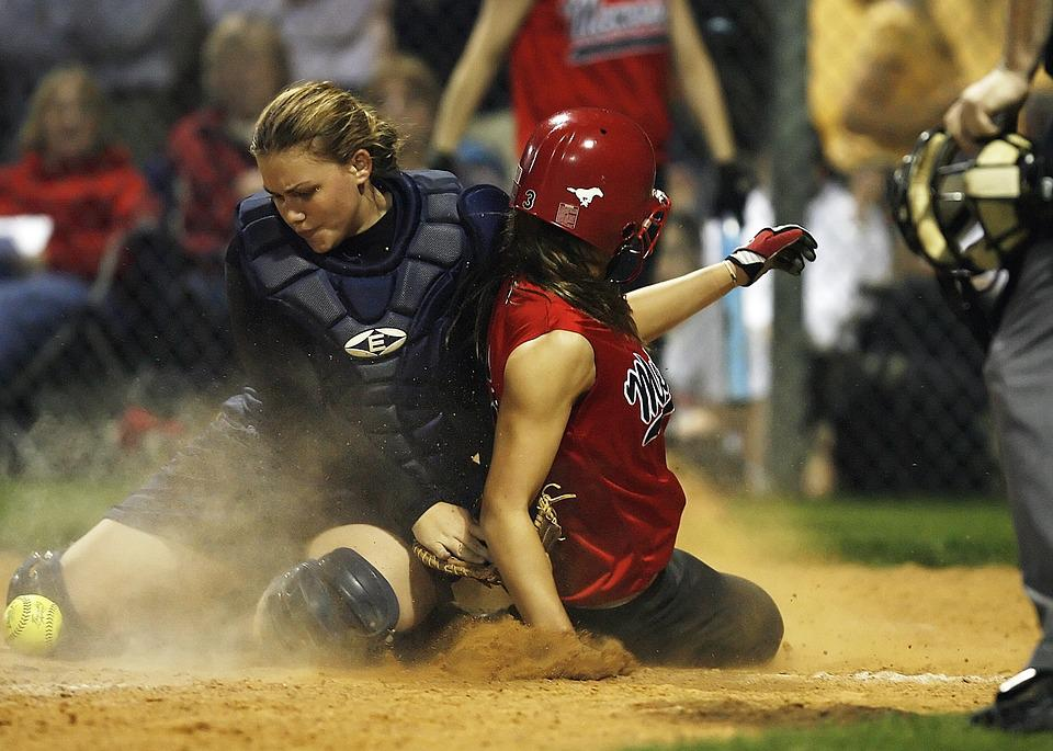 Two women playing softball on the ground, sliding into the base, one is not wearing a helmet