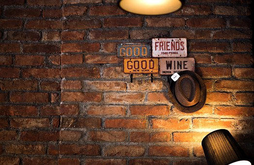 A lit brick wall with words Good friends, good wine for 301 inspirational and motivational quotes