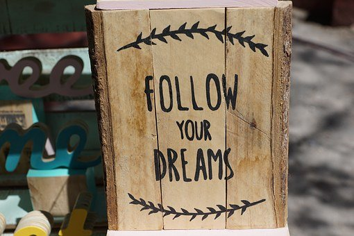 An image showing a wooden block with FOLLOW YOUR DREAMS written on it.