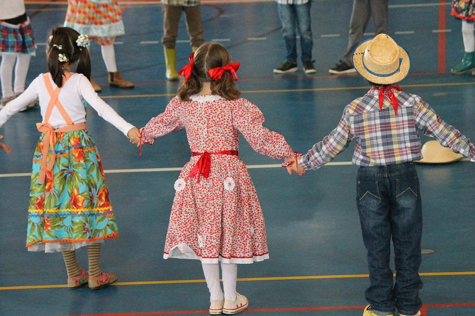Crianças de mãos dadas em círculo, vestidas a caráter para quadrilha de festa junina na escola.
