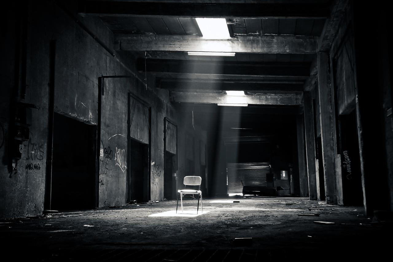 Black and white photo of abandoned room with wooden chair in the foreground