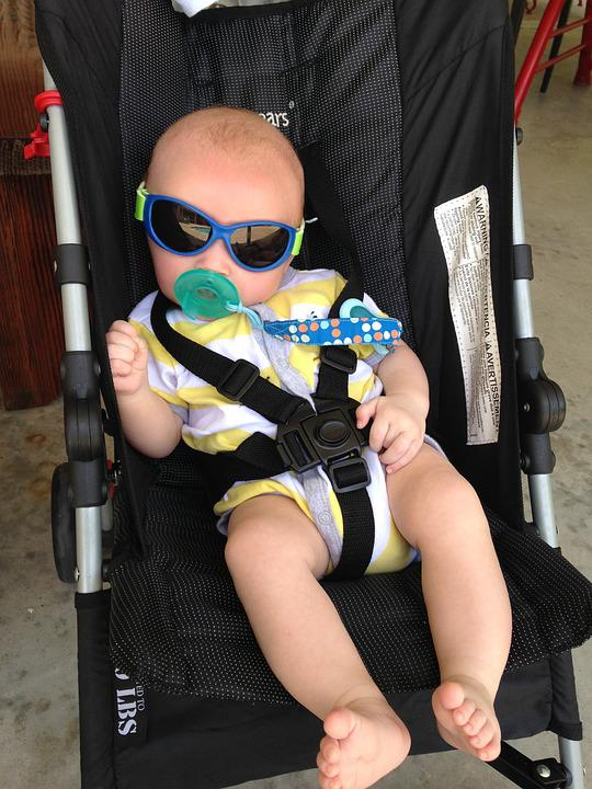 baby on a stroller wearing one of the best infant sunglasses and chewing a pacifier