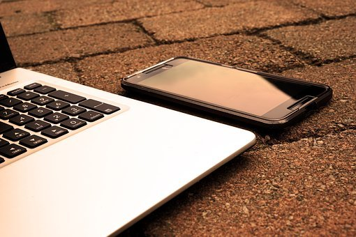 A cellular phone beside a laptop laid on a pebbled floor to signify work from home