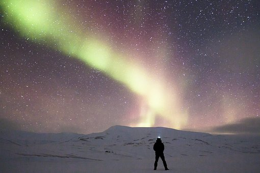 Aurora Boralis, the northern lights shimmering before a man