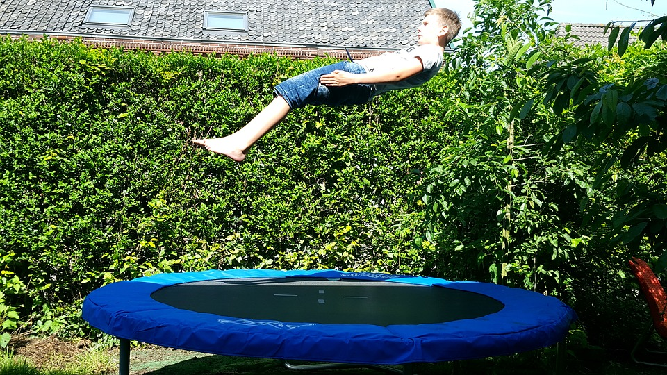 boy jumping on a blue round trampoline