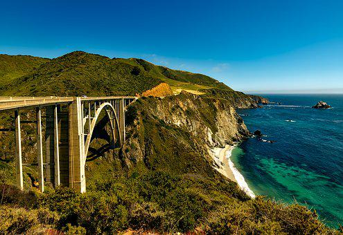 California's Pacific Coastal Highway showing a high bridge, coastal road and sea below