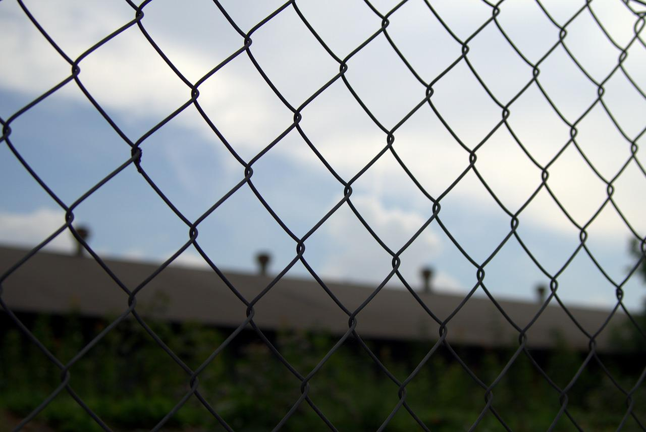 Chain link fence with prison walls in the background