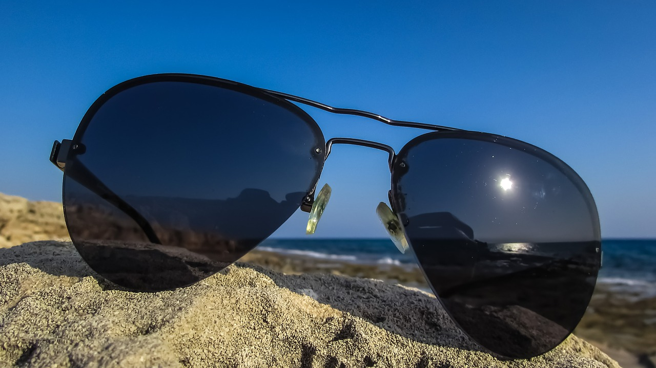 View through polarized sunglasses of harbour ocean and beach stock photo