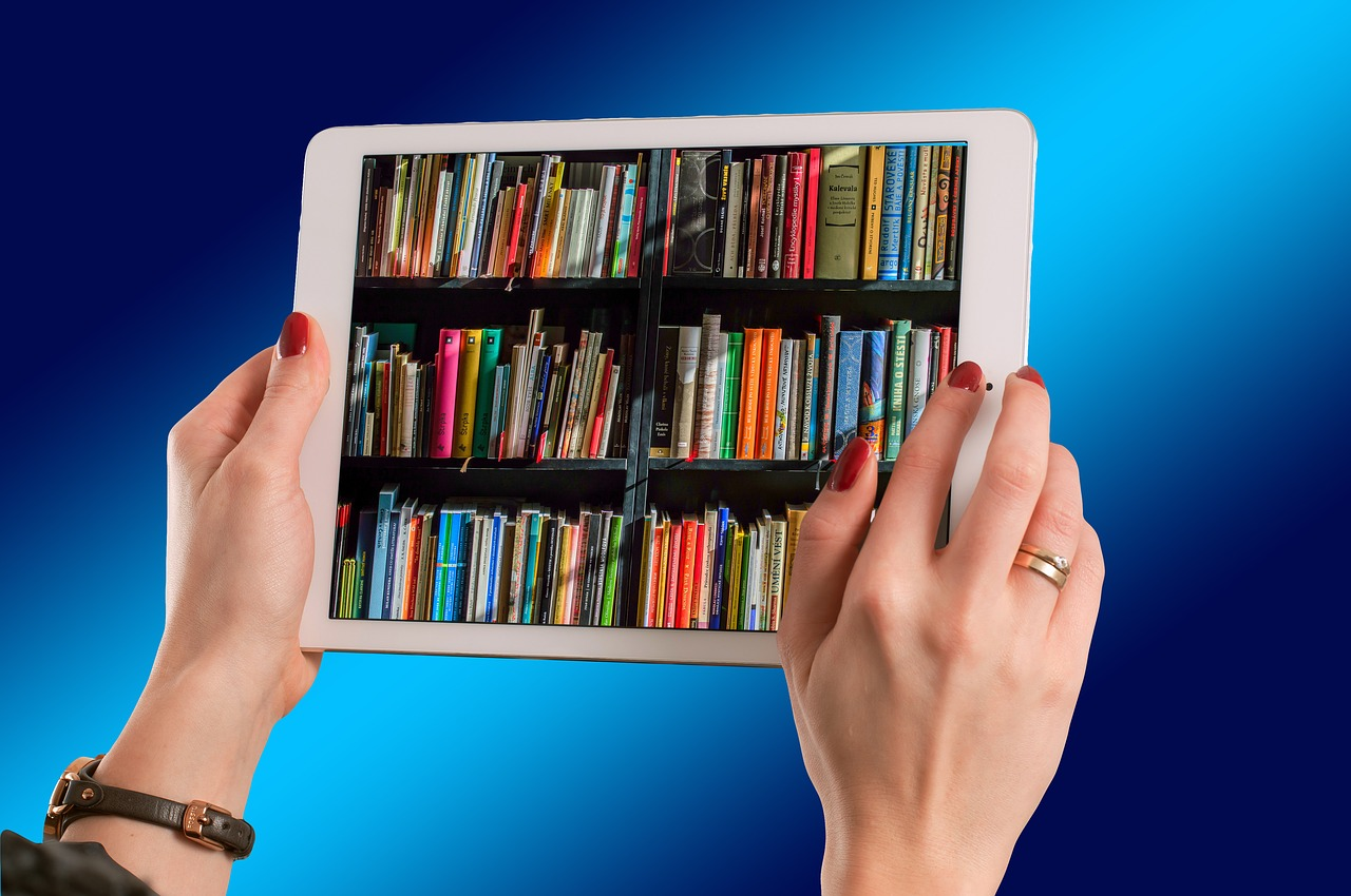 A pair of hands hold a tablet with an image of shelves of books displayed on the screen.