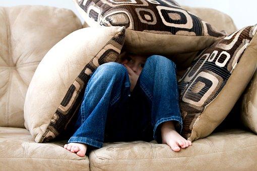 bambino triste che si nasconde tra i cuscini