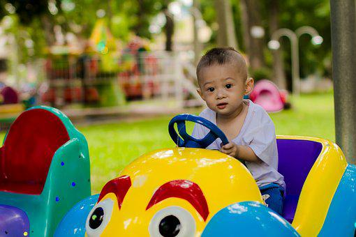 An Asian child in a toy vehicle toshow Aweber Test Drive ads