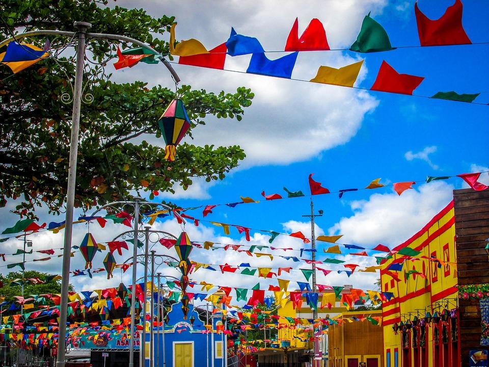 Ambiente externo decorado com bandeirinhas de festa junina e cores vivas (vermelho, azul, amarelo e verde).