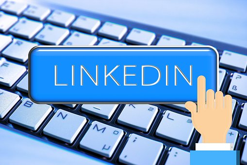 A keyboard in the background and in the foreground the words LINKEDIN written in white over a blue board and a finger hitting it;
