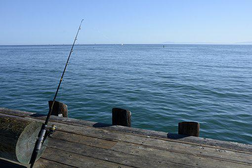 Fishing reel standing against a dock, to signify patience.