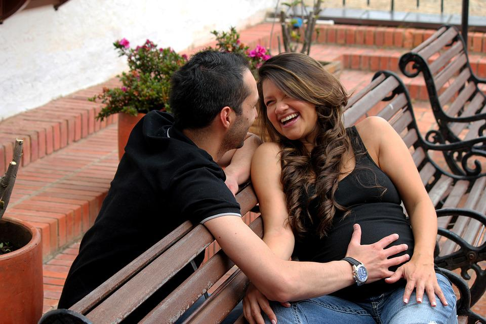 A man and woman laughing on a bench outside with the man rubbing his hand on the womans pregnant belly