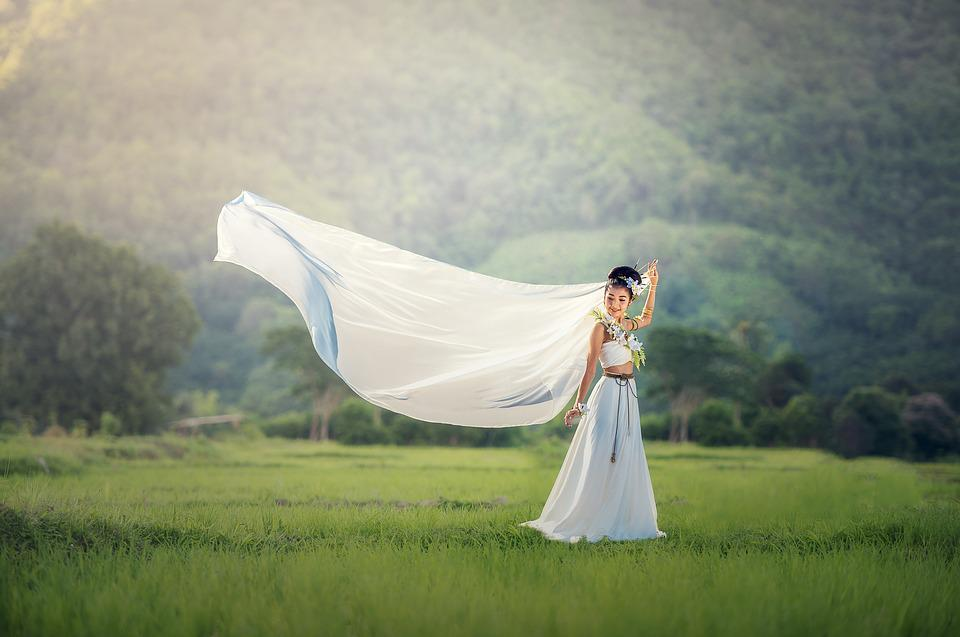bride in field with a veil