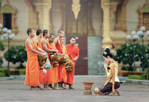 Standing monks praying for a woman on her knees as part of men have advantage over women in blogging