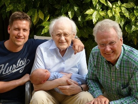 Grandparents and their son with grandma in middle carrying a baby
