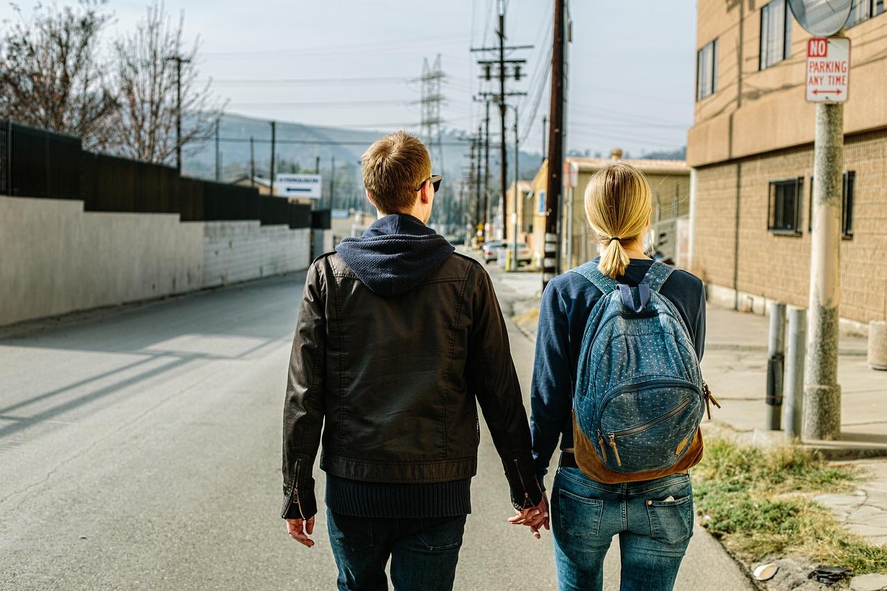 道路の上で手をつなぎ歩いている男女の画像