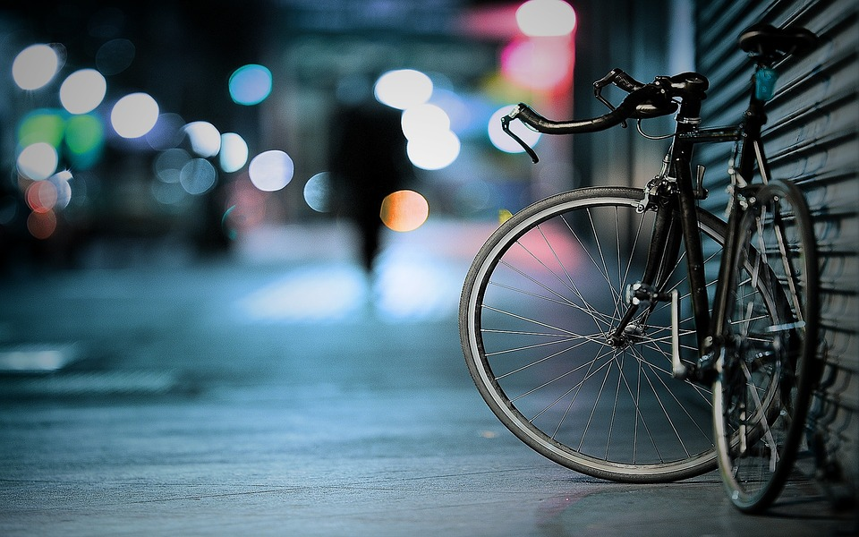 A bicycle is propped up against a building with bright lights in the background