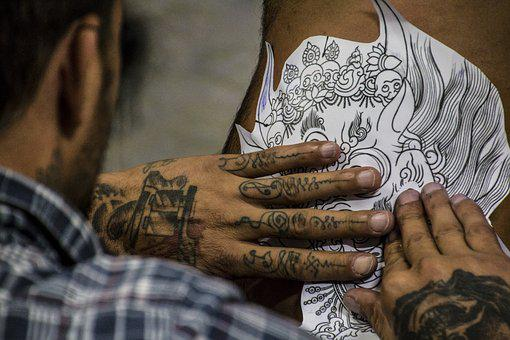An artist putting a design on a body to be tattoed
