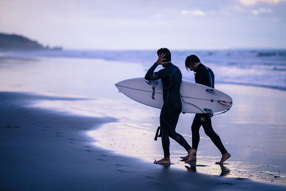 two men walking on beach with surf board