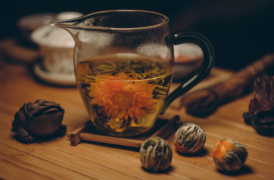 Image of a blooming tea flower in a clear mug on a wooden table.