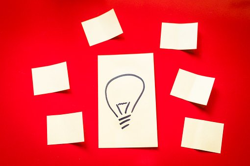 A bright red background with 6 white square post-its around a big traingular in the middle with drawing of a light bulb on it