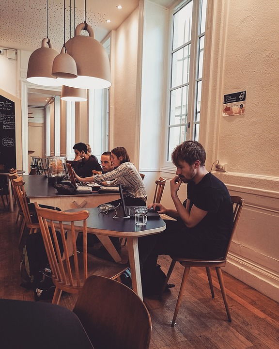 A young man browsing the internet on his laptop in a café.