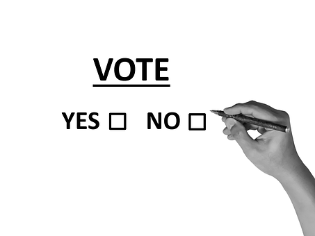 A hand with a pen about to vote Yes or No.