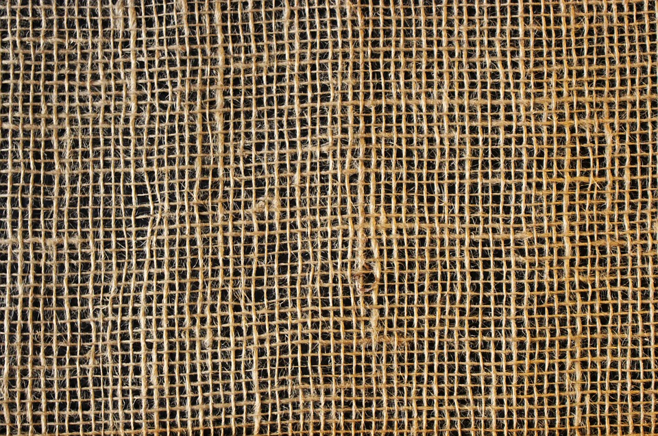 ID: a sample of sackcloth, a light brown, loosely woven fabric against a dark background.