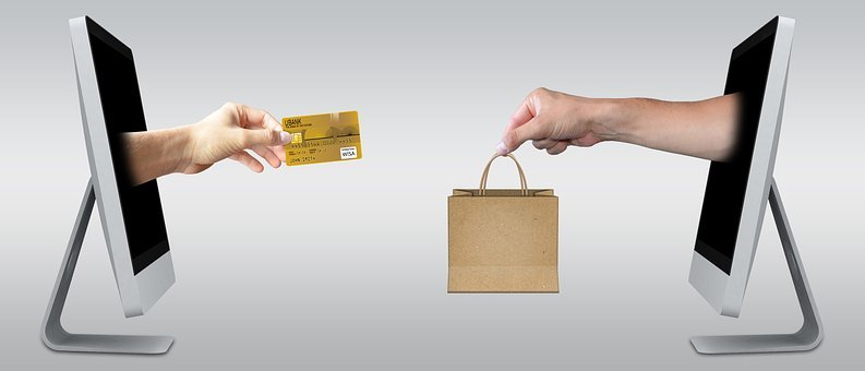 A hand sticking out of a computer screen tending a credit/debit card towards another sticking out of a screen with a paper bag to signify Selling