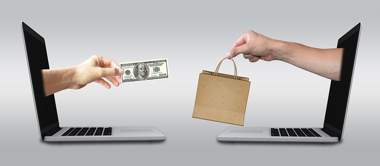 A hand sticking a dollar bill out of a computer and another one on the right with a shopping bag
