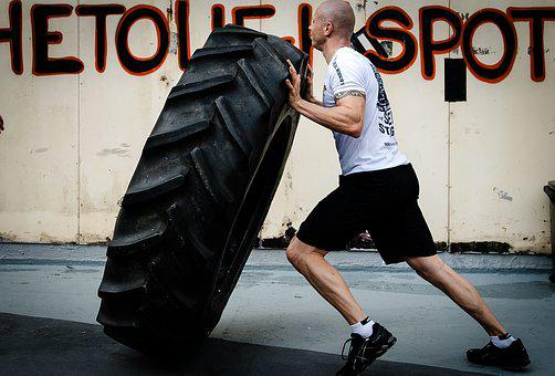 A man rolling a caterpillar tyre to signify hard training to succeed in affiliate marketing
