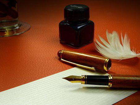 fountain pen beside a bottle of ink and feather