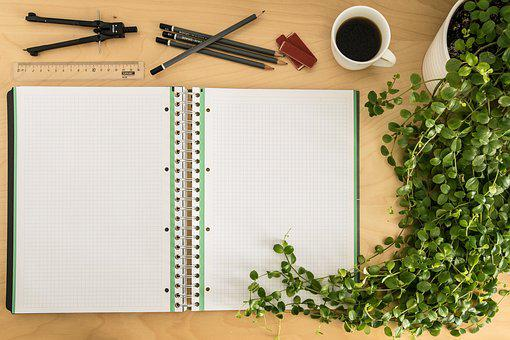 An opened exercise book beside a flower pot and with mathematical instruments and a cup of coffee