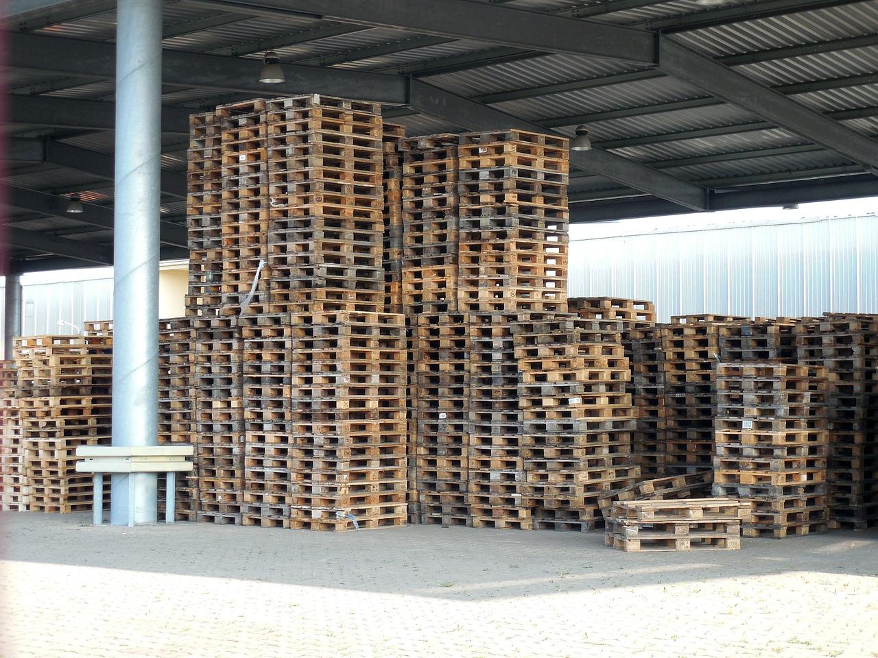 Holzpaletten gestapelt auf einer überdachten Lagerfläche